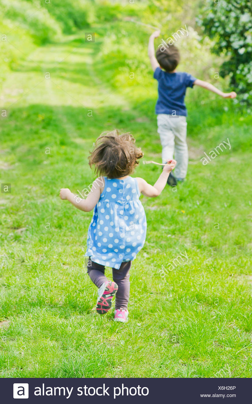 Children running on path through countryside - Stock Image