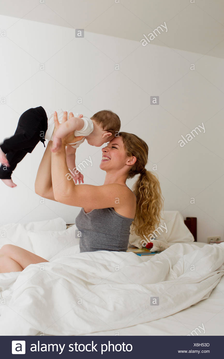 Mother holding baby boy up in mid air - Stock Image