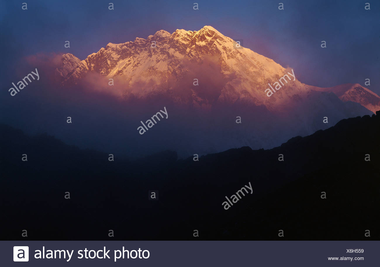 The mountain Nuptse which is Everest's southern neighbour emerges from mist and cloud in a dramatic sunset - Stock Image