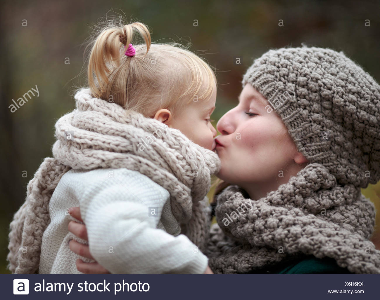 Young woman kissing her little daughter in autumn Stock Photo