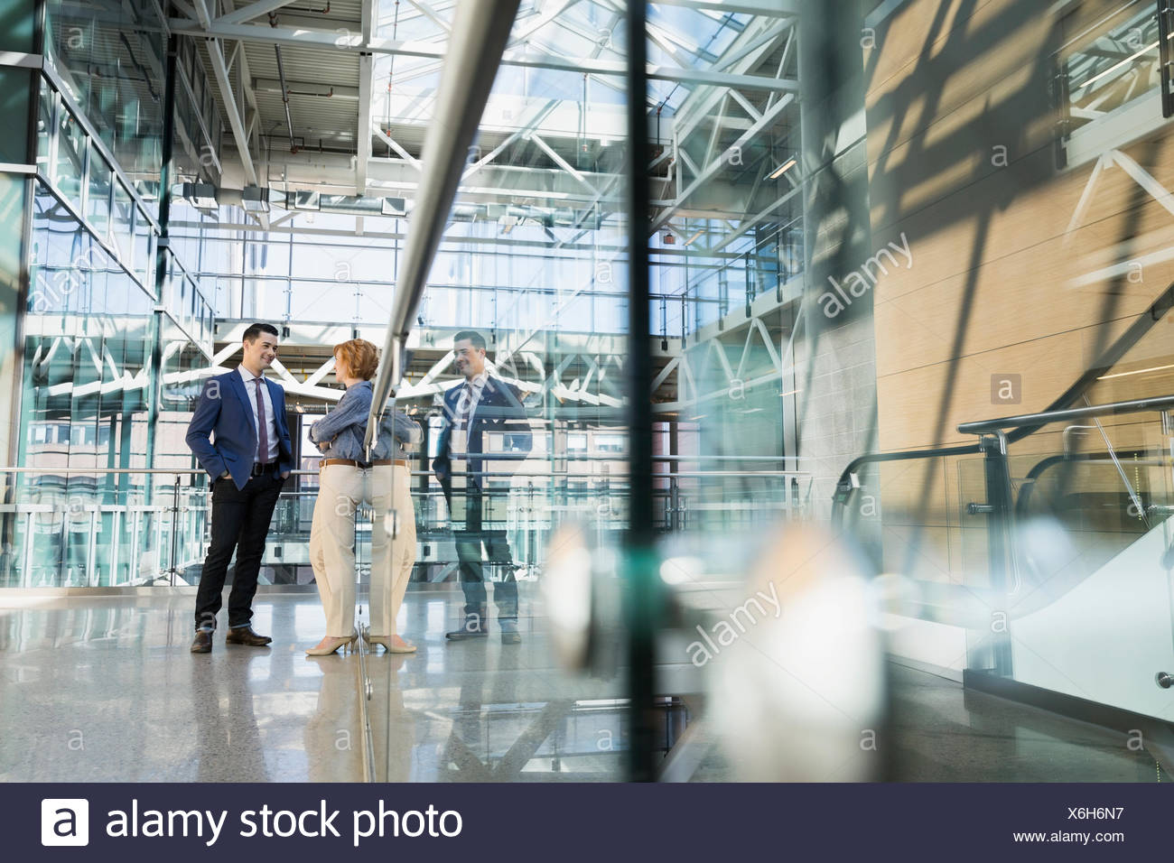 Business people talking in atrium - Stock Image