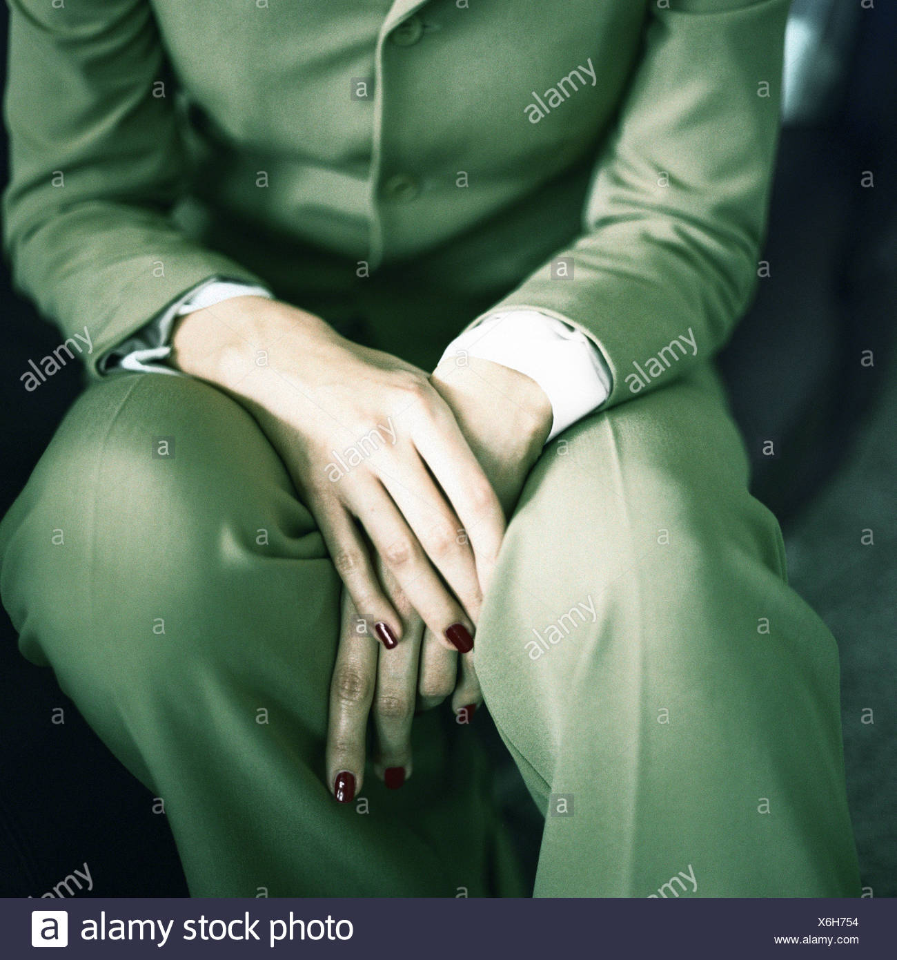 Businesswoman sitting, mid-section, close-up - Stock Image