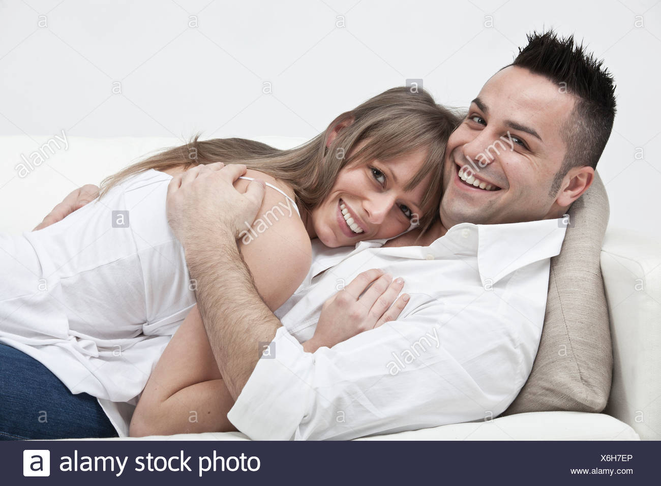 Smiling couple hugging on couch - Stock Image