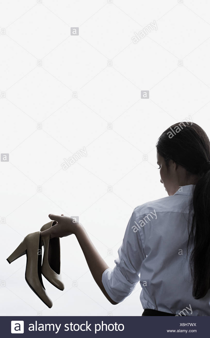 A businesswoman holding high heeled shoes - Stock Image
