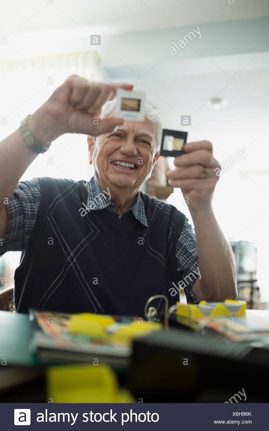 Senior man looking through old slides - Stock Image