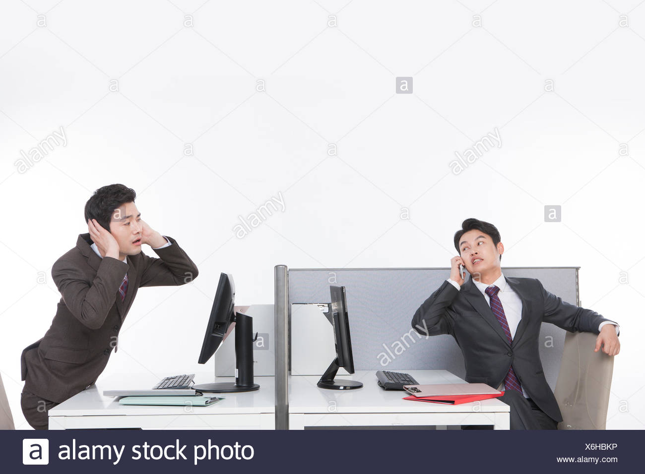 One businessman yelling to his cellphone and another closing ears - Stock Image