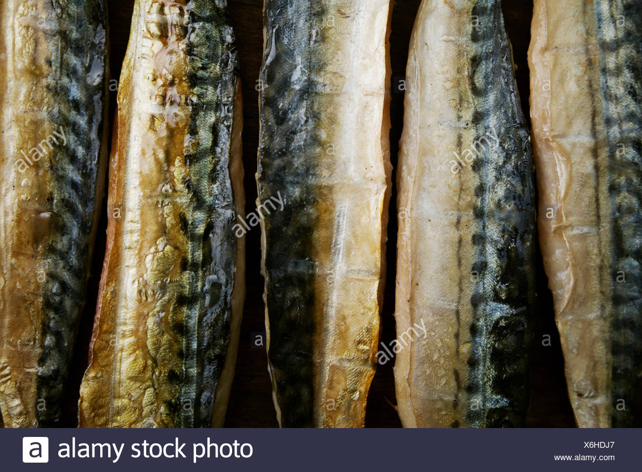 Smoked fish fillets laid out in a row. - Stock Image