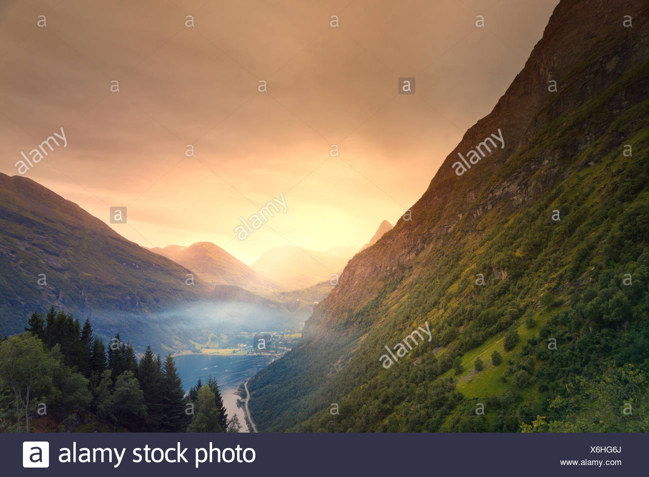 Norway, More og Romsdal, Sunnmore, Geiranger, Elevated view of misty lake in mountain valley - Stock Image
