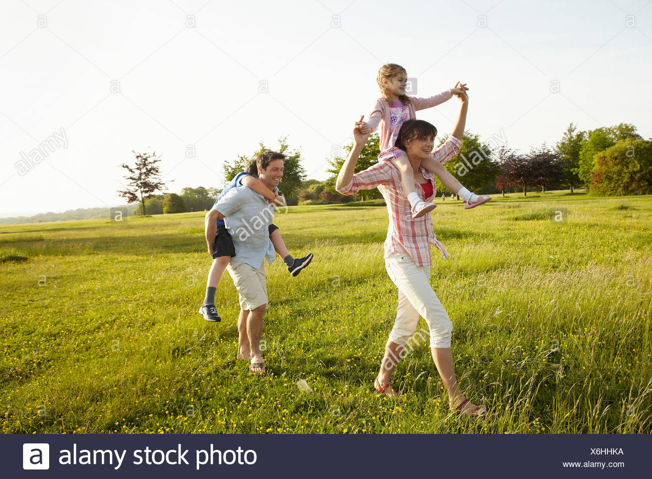 A family, two parents outdoors in the summer giving piggybacks to two children. - Stock Image