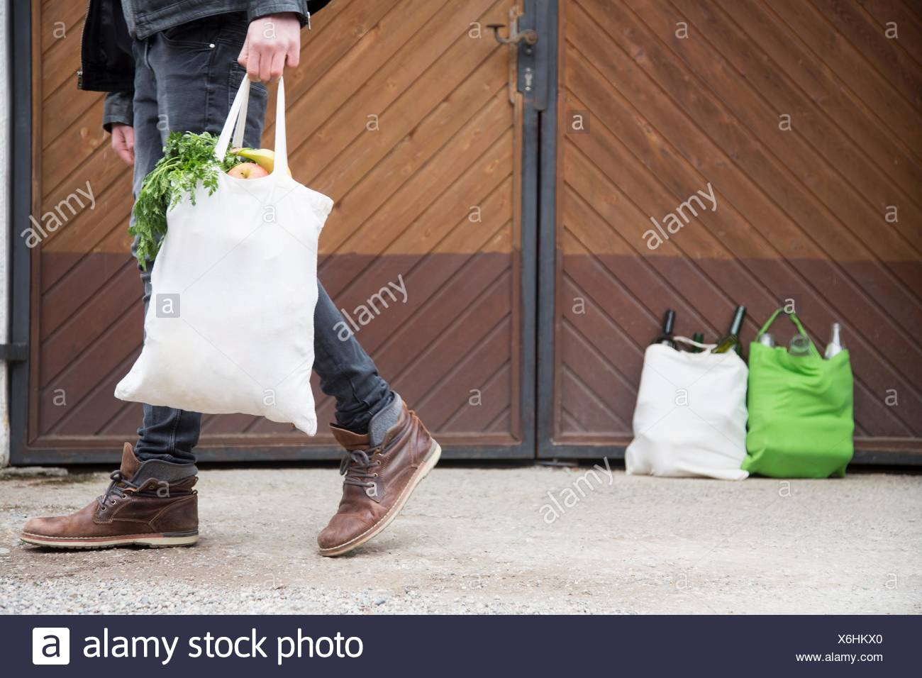 Teenage boy carrying reusable shopping bag full of fruit and veg, with bottles for recycling in yard - Stock Image