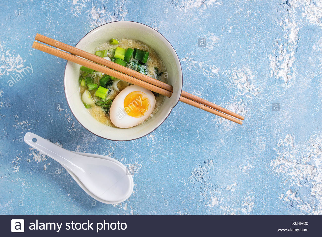 Bowl with asian style soup with scrambled eggs, half of marinated egg, spring onion, spinach served with wood chopsticks and spoons over blue texture  - Stock Image