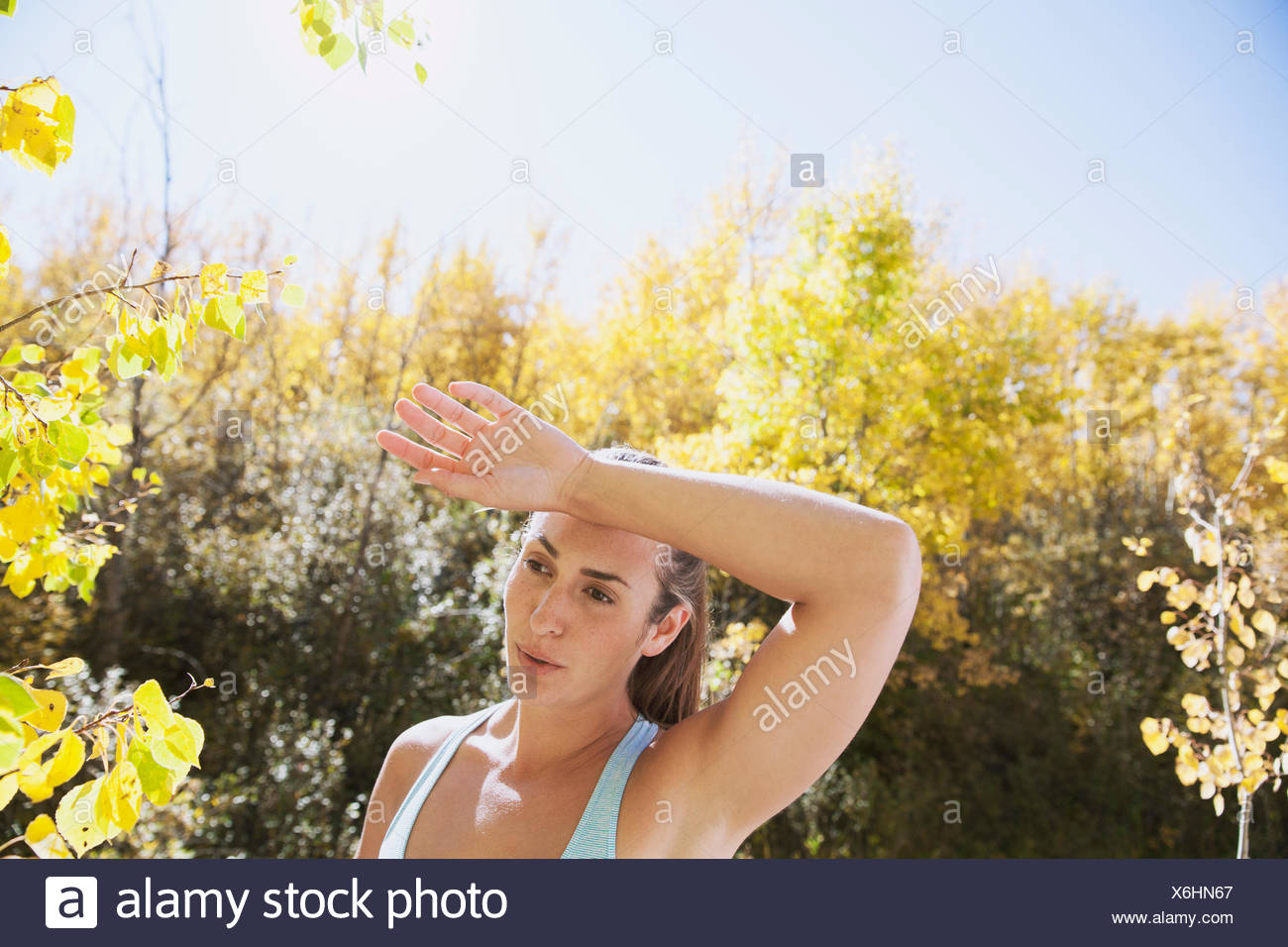 Woman wiping brow during outdoor workout. - Stock Image