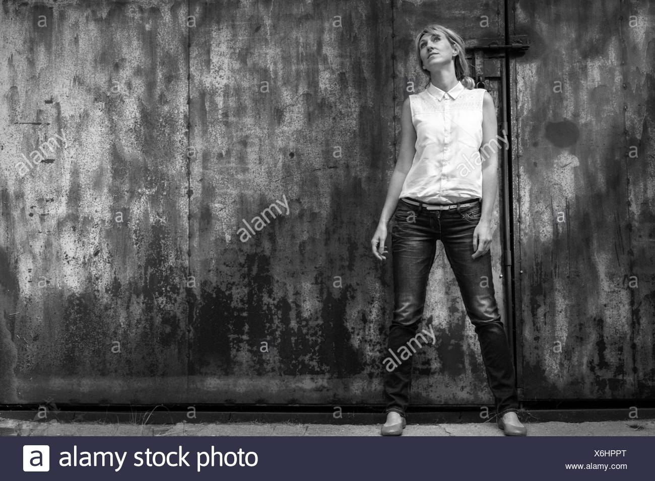 Full Length Front View Of Woman Standing Against Gate - Stock Image