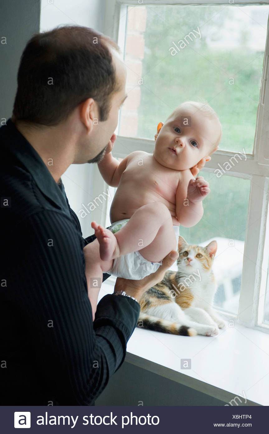 Father by window holding baby boy (6-11 months) - Stock Image