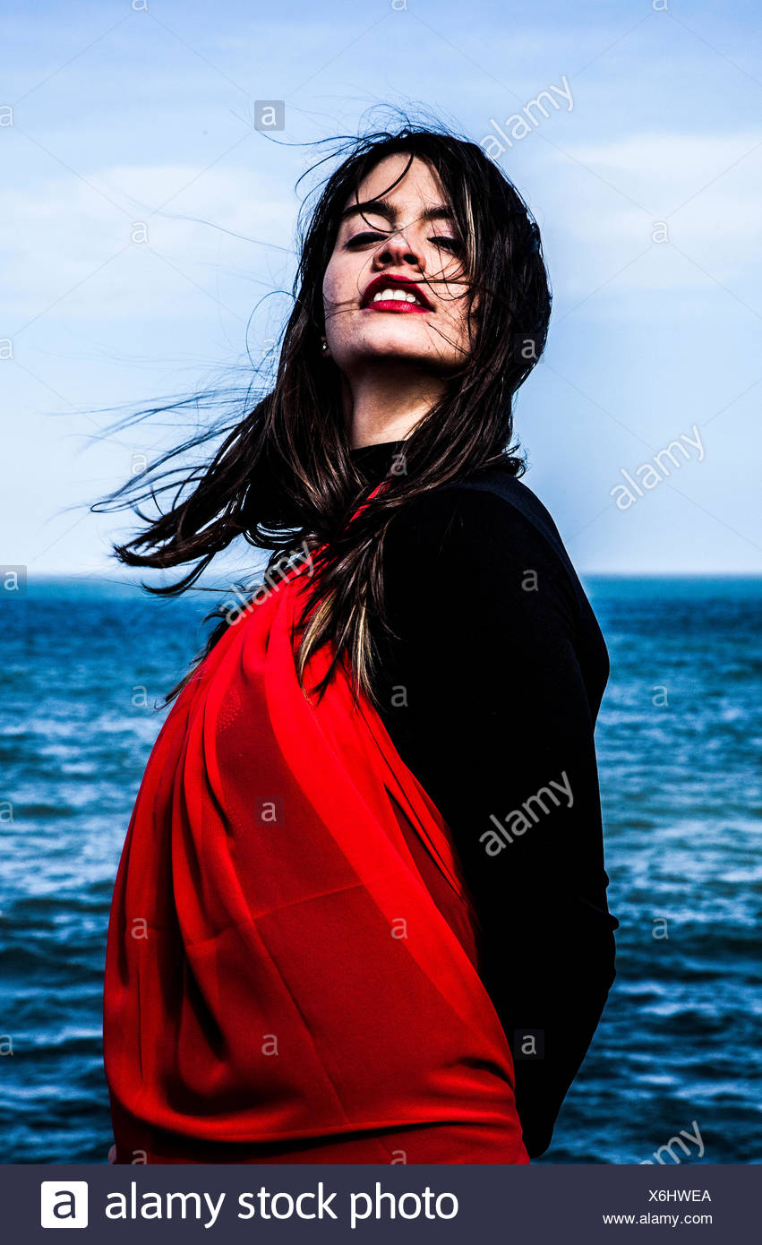 Portrait of a young woman by the sea - Stock Image