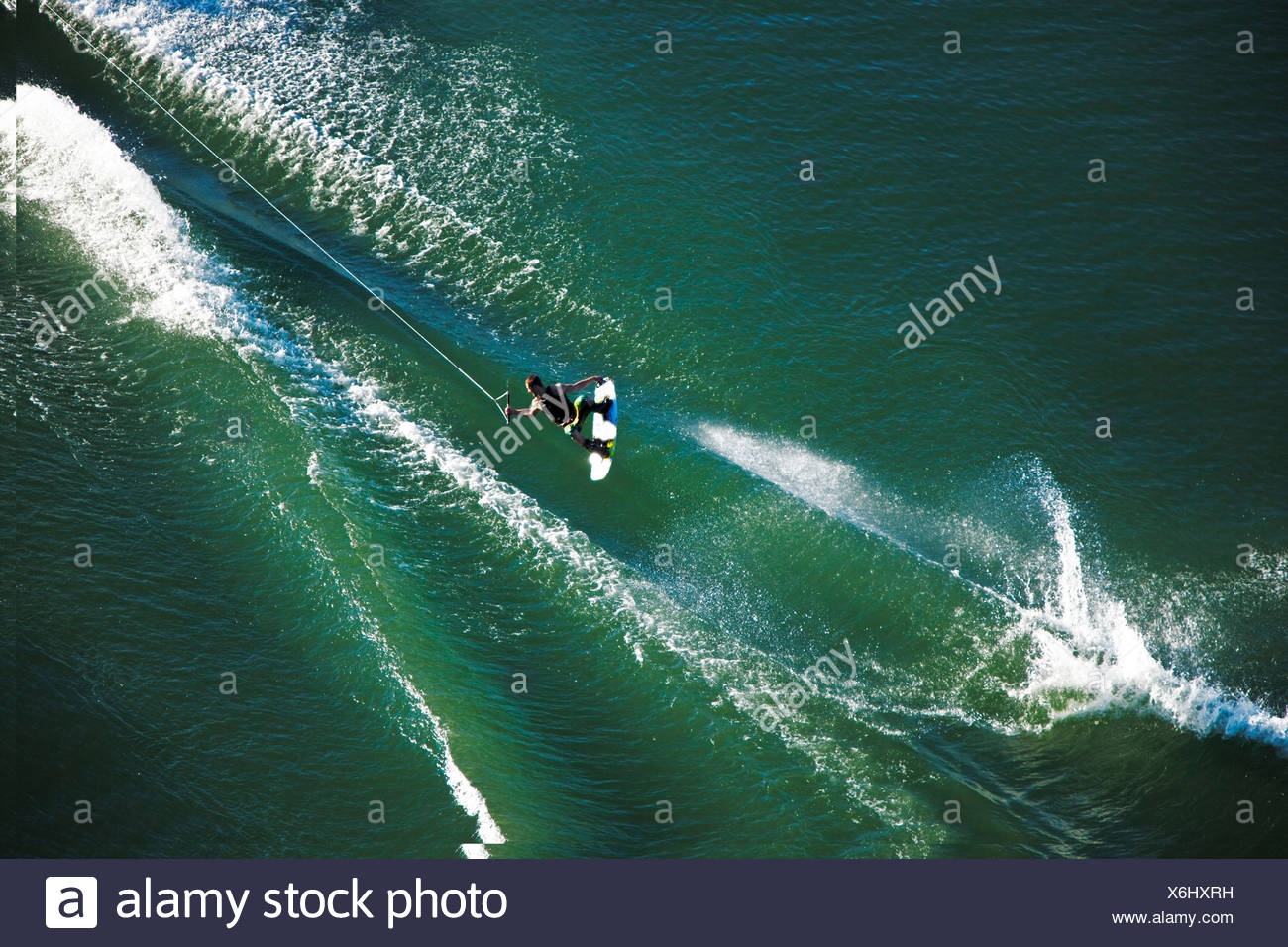 A athletic wakeboarder jumps the wake going huge on a calm day in Idaho. - Stock Image