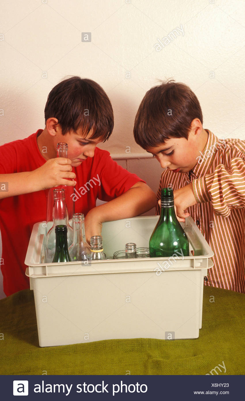 portrait two young boys sorting items for recycling - Stock Image