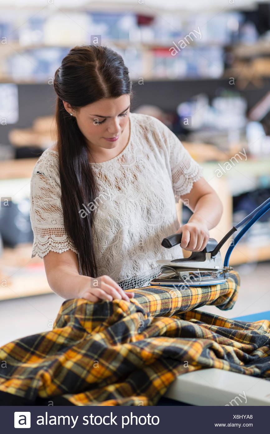 Young seamstress ironing tartan jacket in workshop - Stock Image