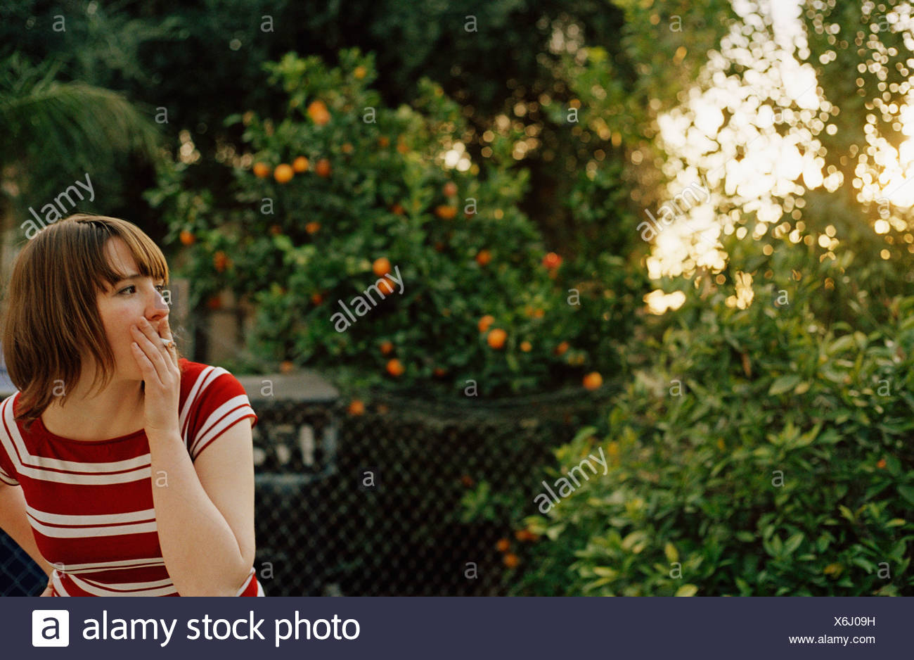 Young woman smoking a cigarette in a back yard - Stock Image