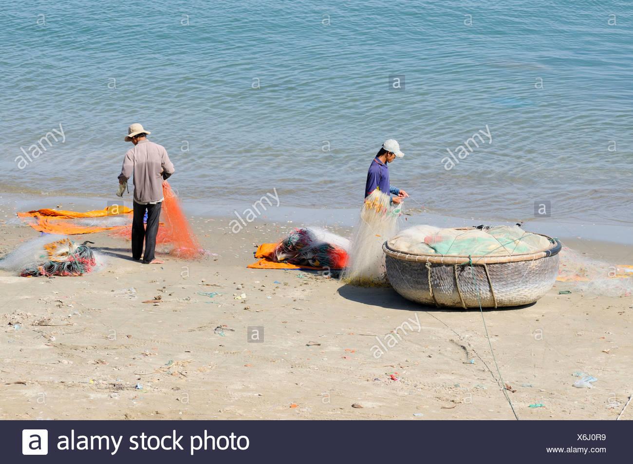 Two fishermen on a beach repairing their fishing nets, Mui Ne, Vietnam, Asia - Stock Image