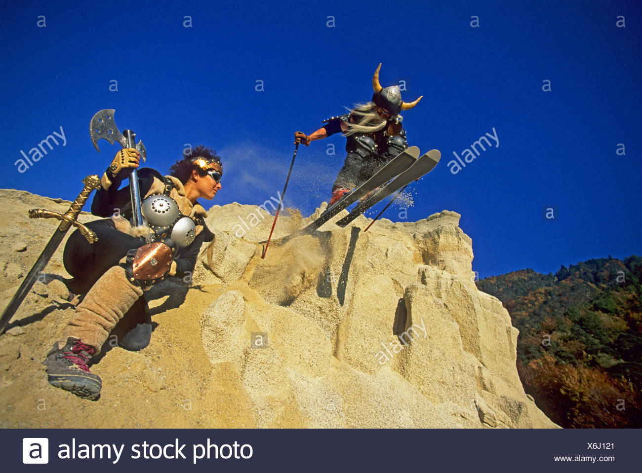freeride skier disguised as viking going downhill on shingle slope - Stock Image