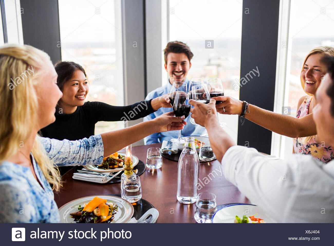 Friends toasting with red wine and enjoying at Sky bar restaurant Stock Photo