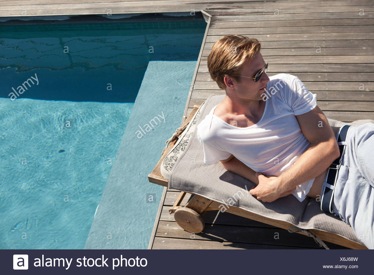 Man relaxing by swimming pool Stock Photo