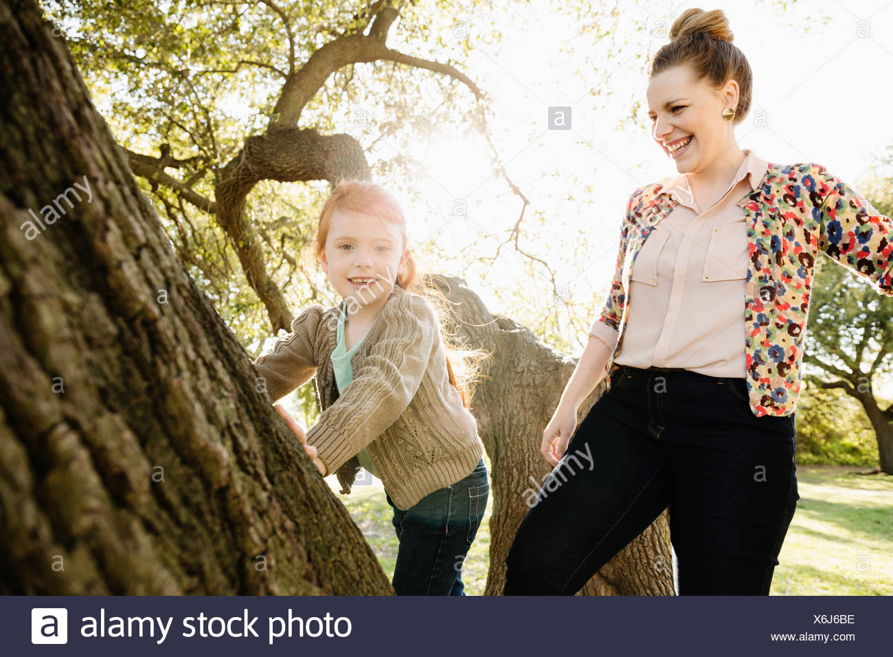 Portrait of mid adult mother watching daughter climb tree - Stock Image