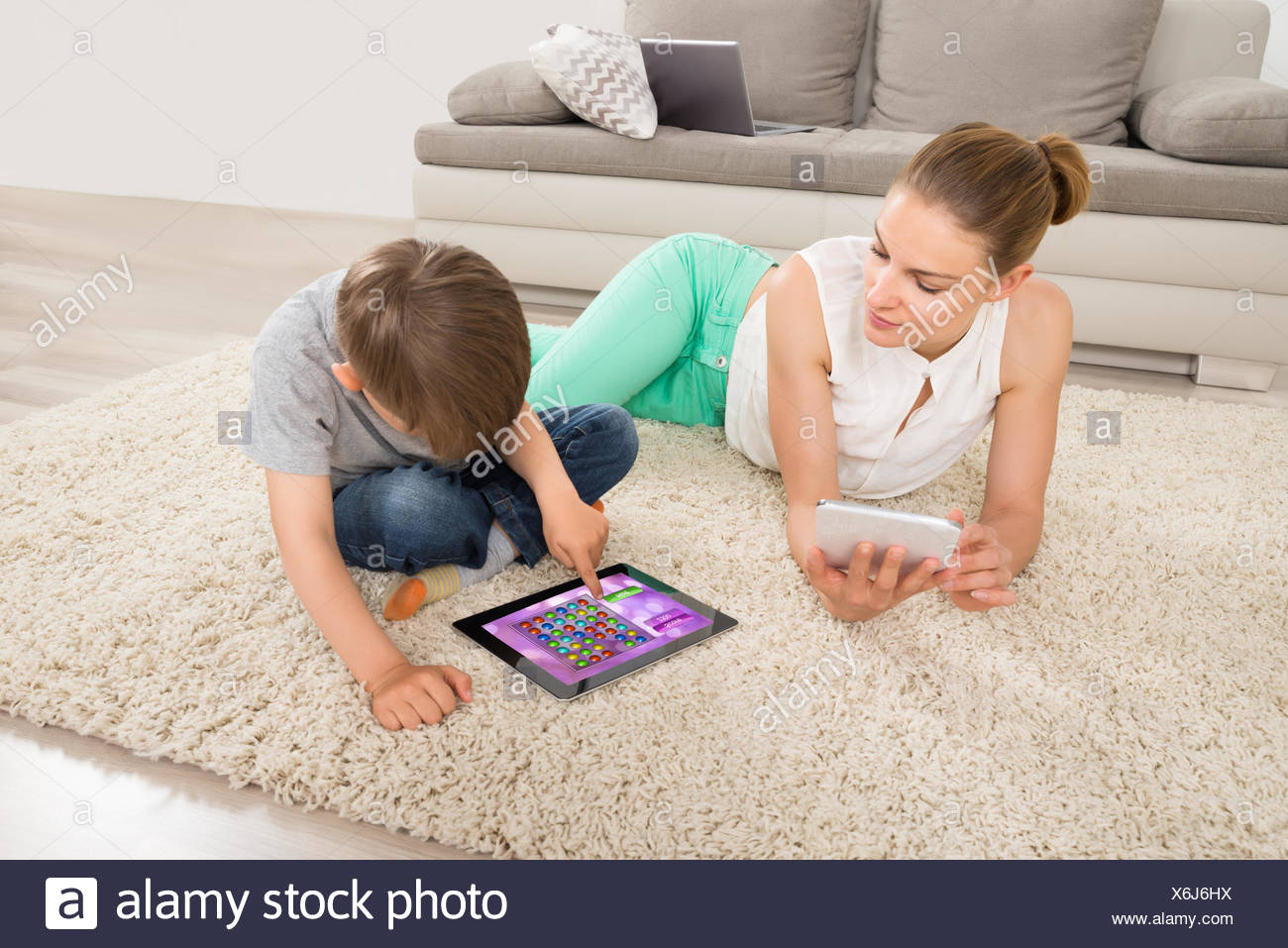 Boy Playing Game On Digital Tablet With Mother Stock Photo