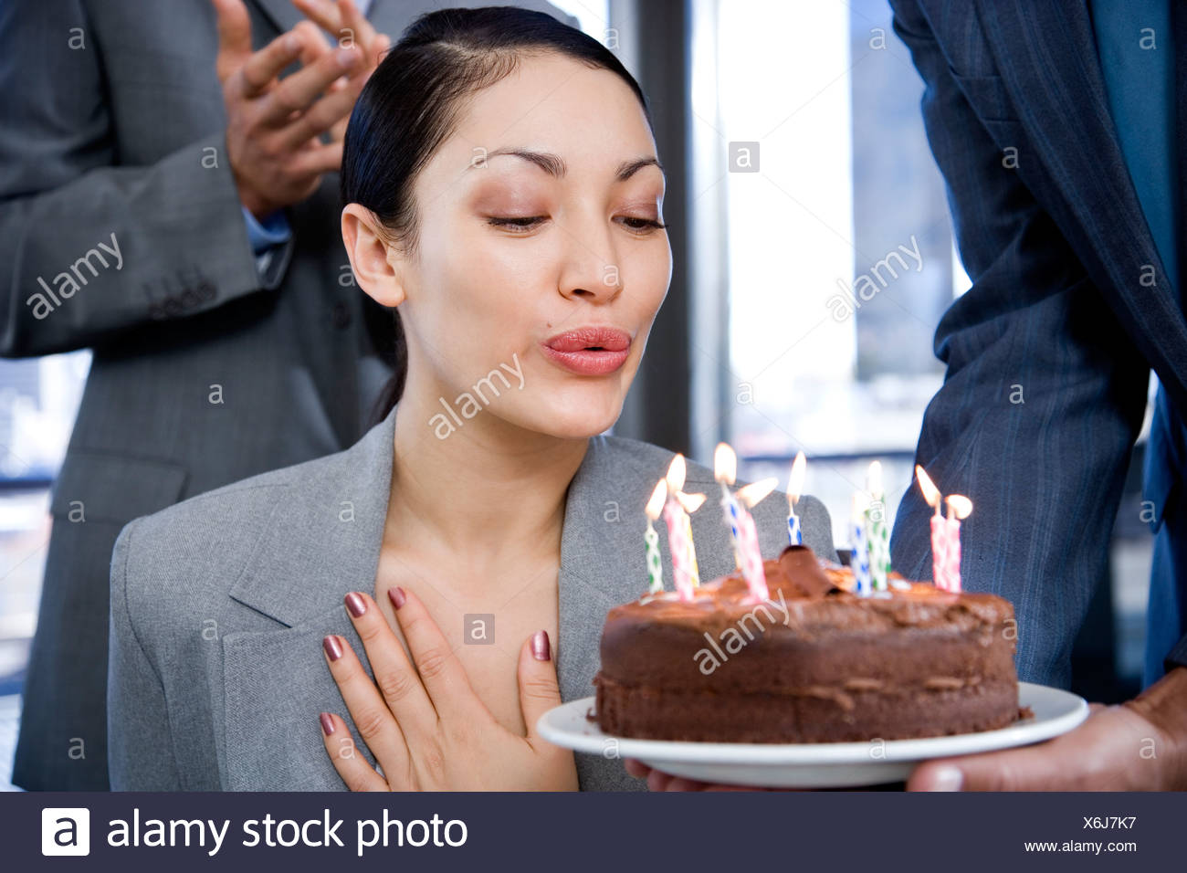 A Businesswoman Blowing Out Her Birthday Cake Candles At The Office