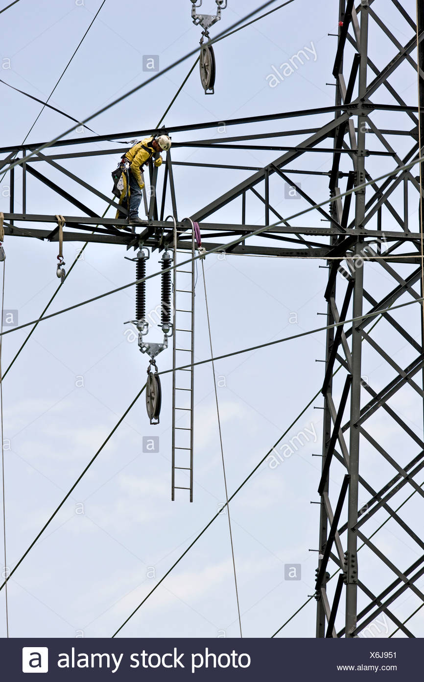 High voltage technician installing a new high-voltage power line - Stock Image