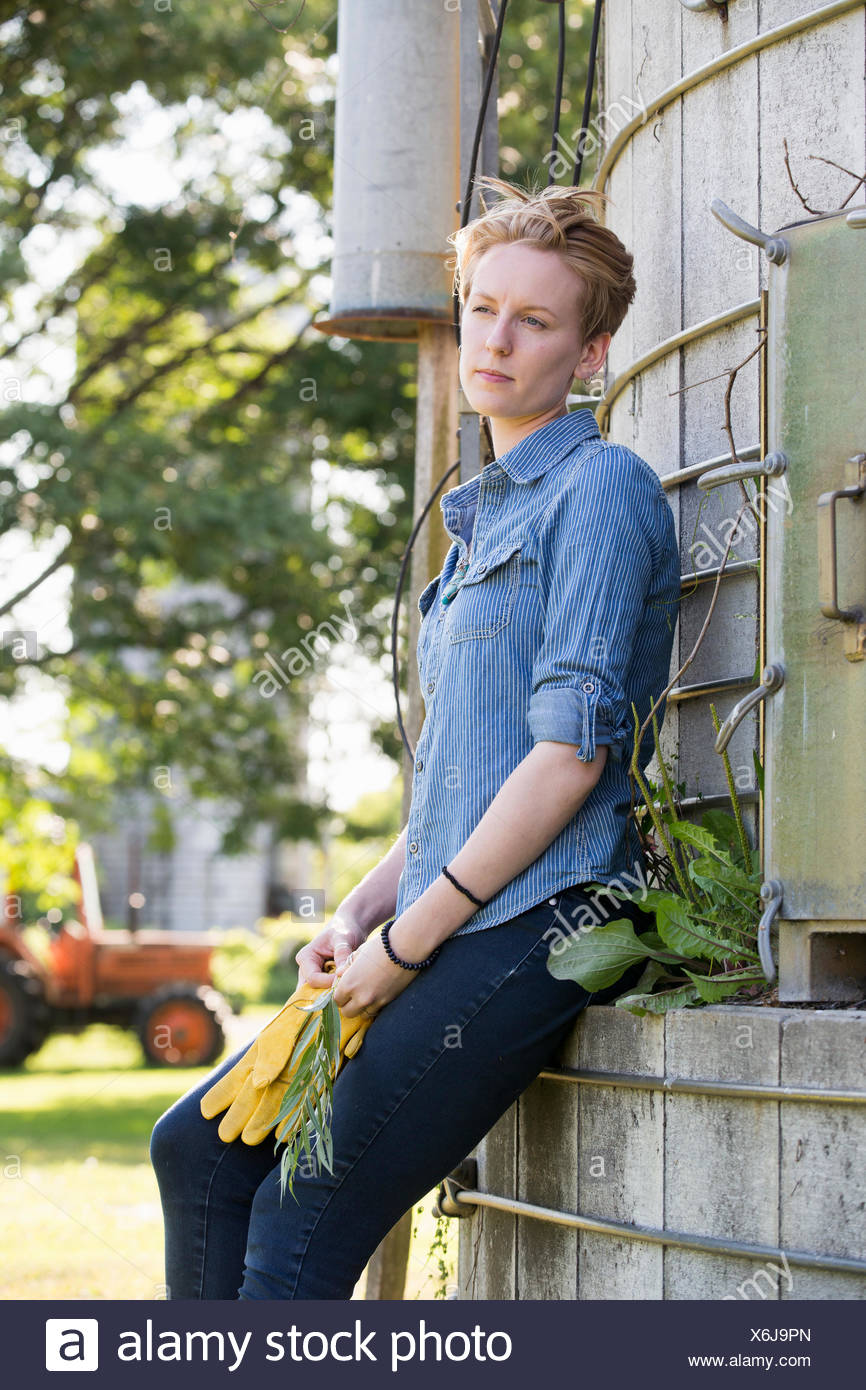 Young woman on a working farm, taking a break in the shade of a silo. - Stock Image