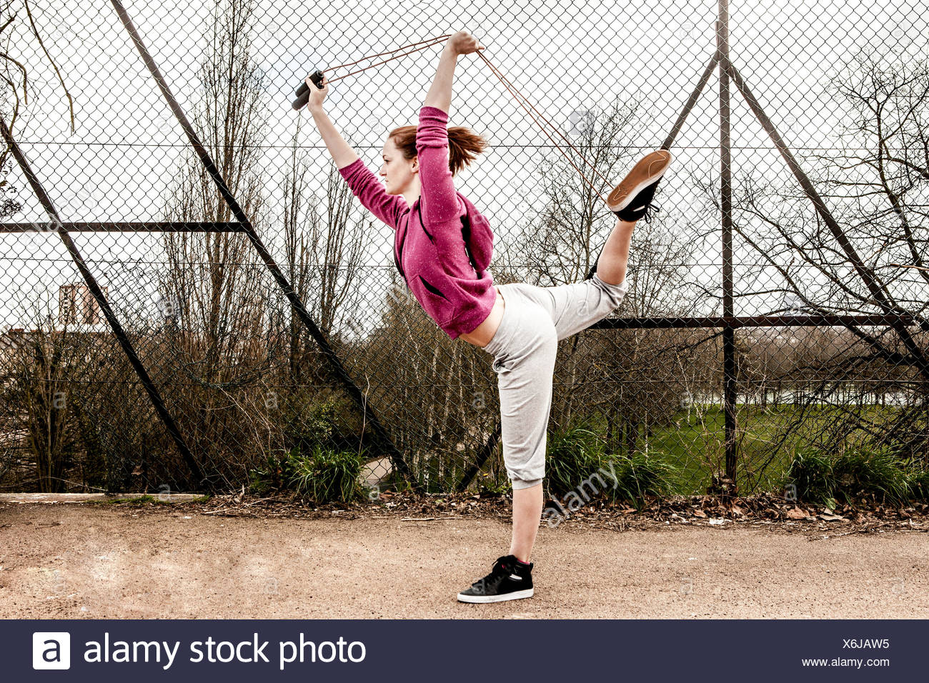 Woman in hoodie pulling pilates rope from behind bent leg - Stock Image