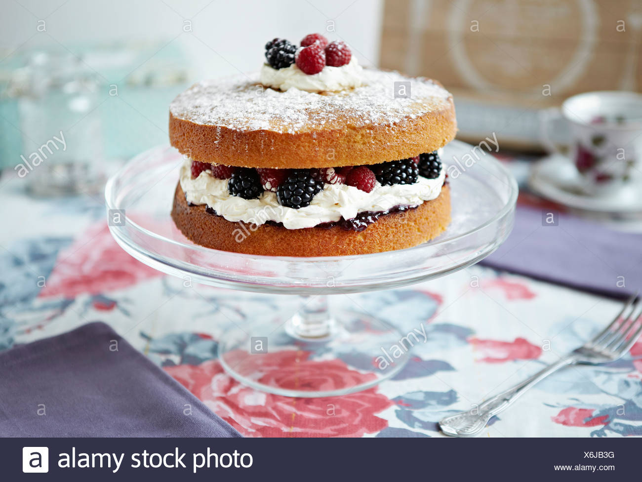 Sponge cake with berries on platter - Stock Image