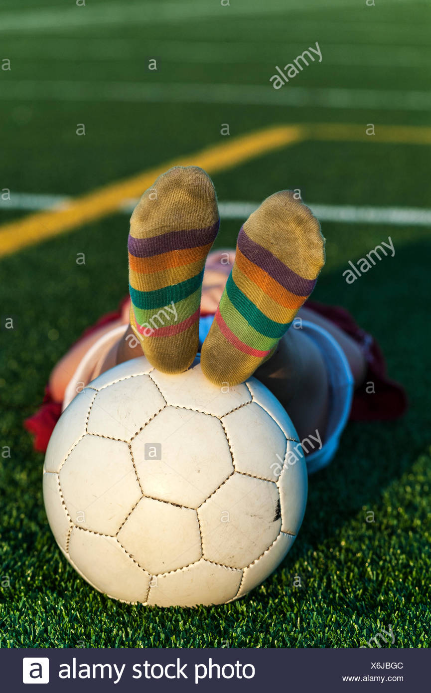 Tired girl with soccer ball after practice. - Stock Image