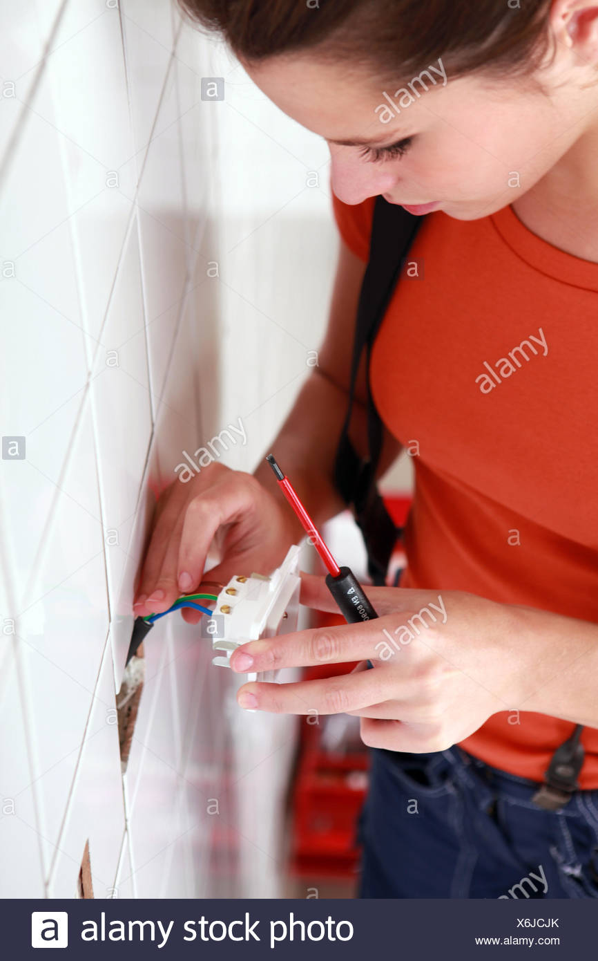 handywoman setting an outlet in a wall - Stock Image