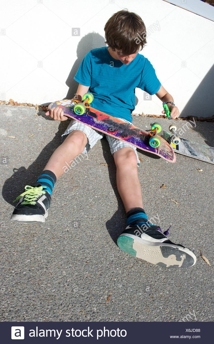 Teenage boy sitting on ground preparing skateboard - Stock Image