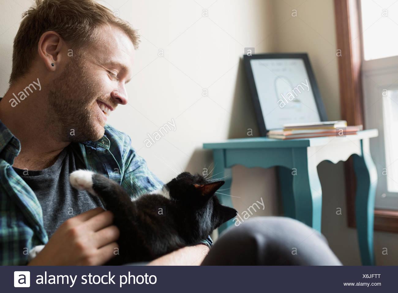 Affectionate man petting cat - Stock Image
