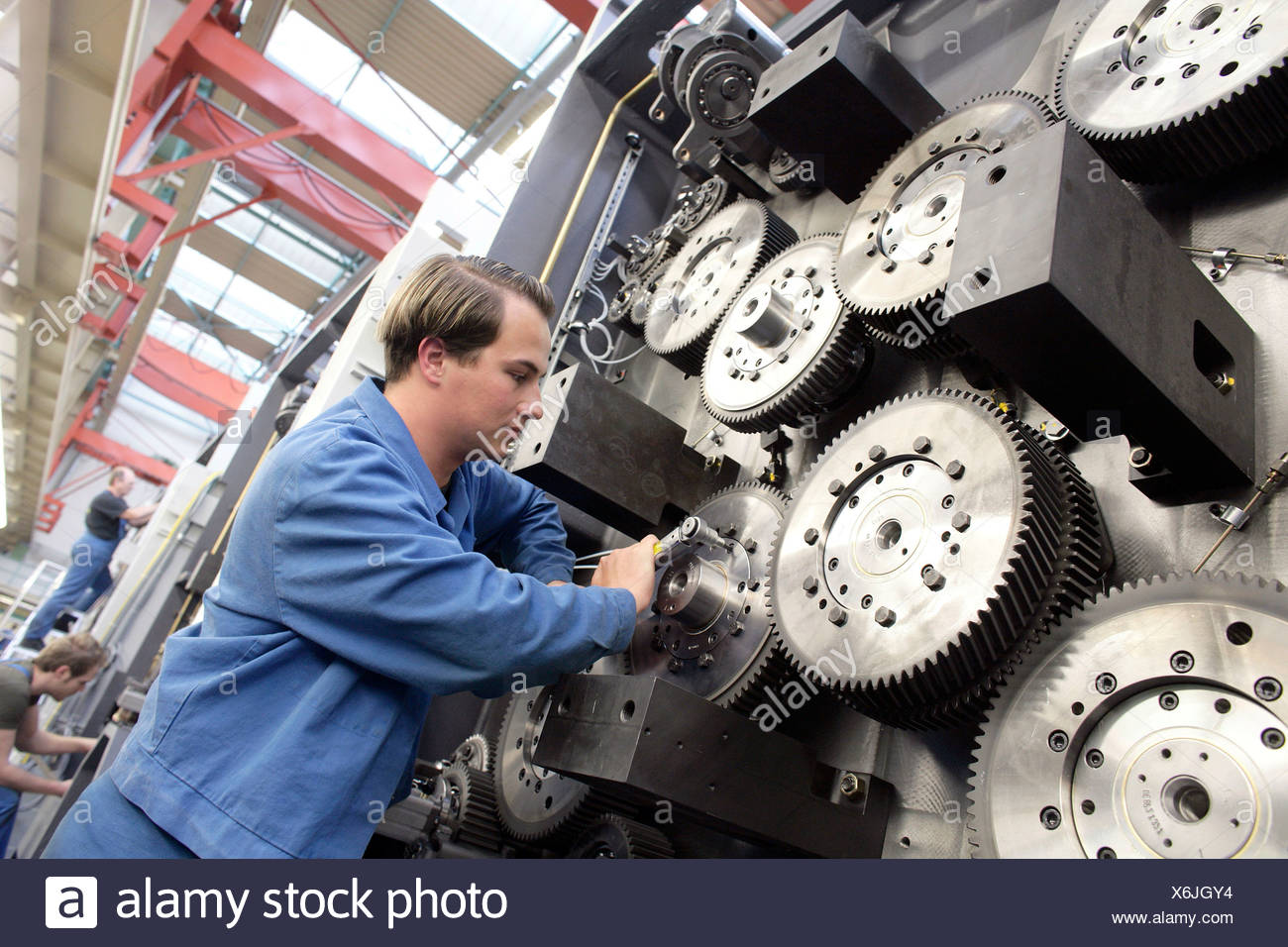 Laborer tightening the gears of an impression cylinder of a reel-fed offset printing machine, manufacture, Production MAN Rolan - Stock Image