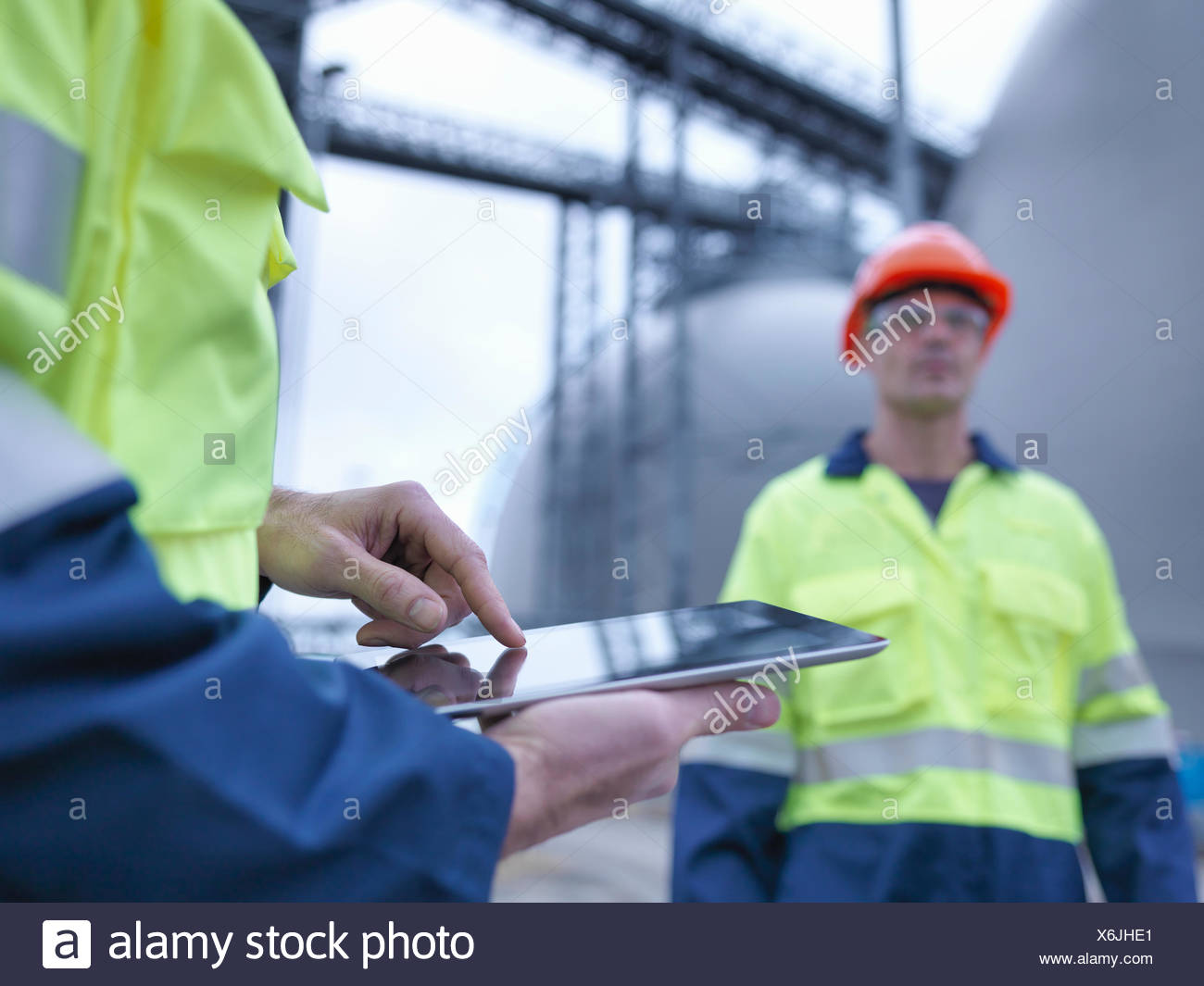 Workers using digital tablet at biomass facility, close up - Stock Image