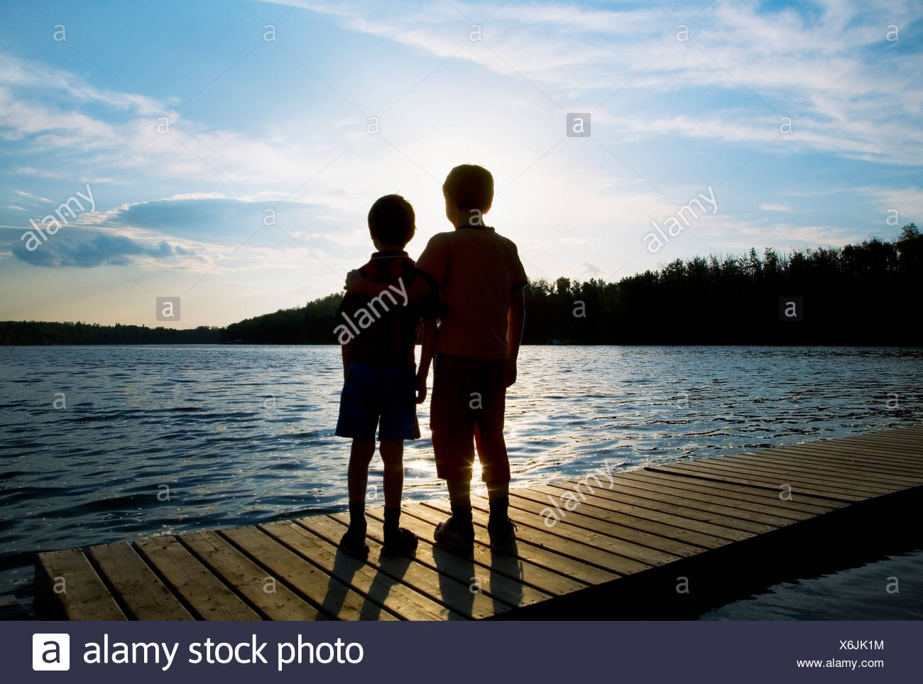 Silhouette of children on a dock Stock Photo