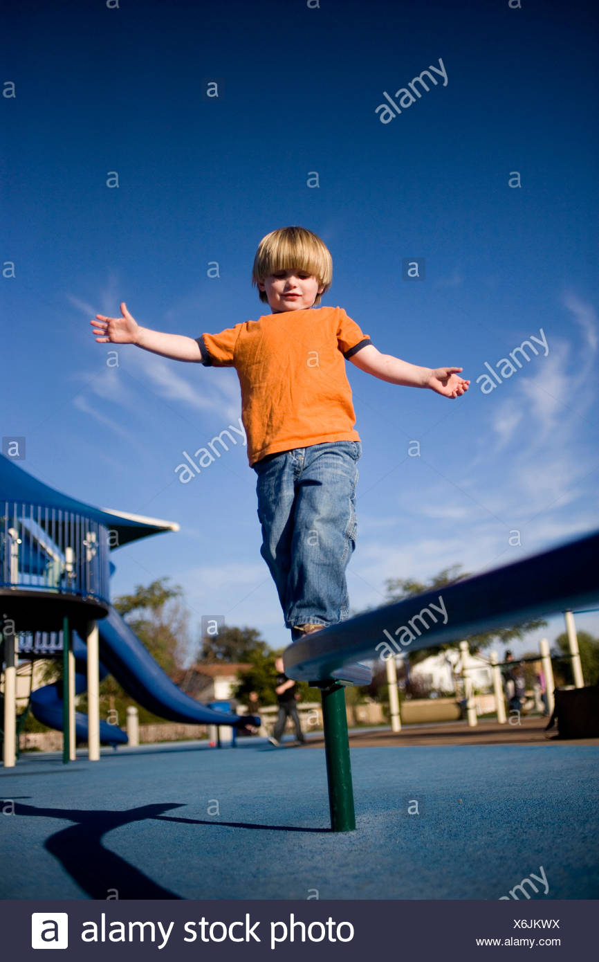 Boy walking on balance beam in playground - Stock Image