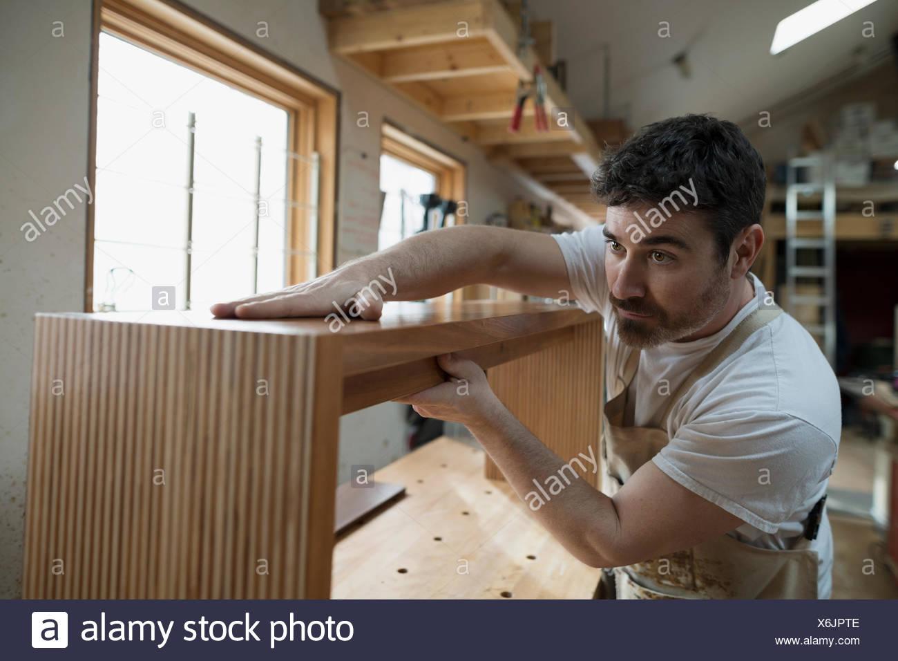 Carpenter assembling furniture in workshop - Stock Image