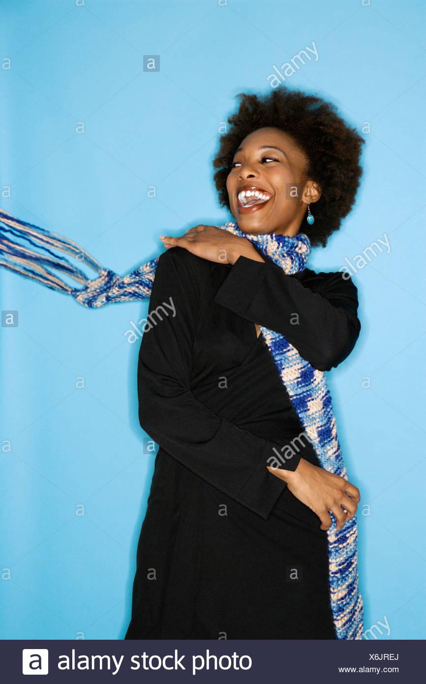 Half length studio portrait of smiling happy woman flinging scarf over shoulder on blue background - Stock Image