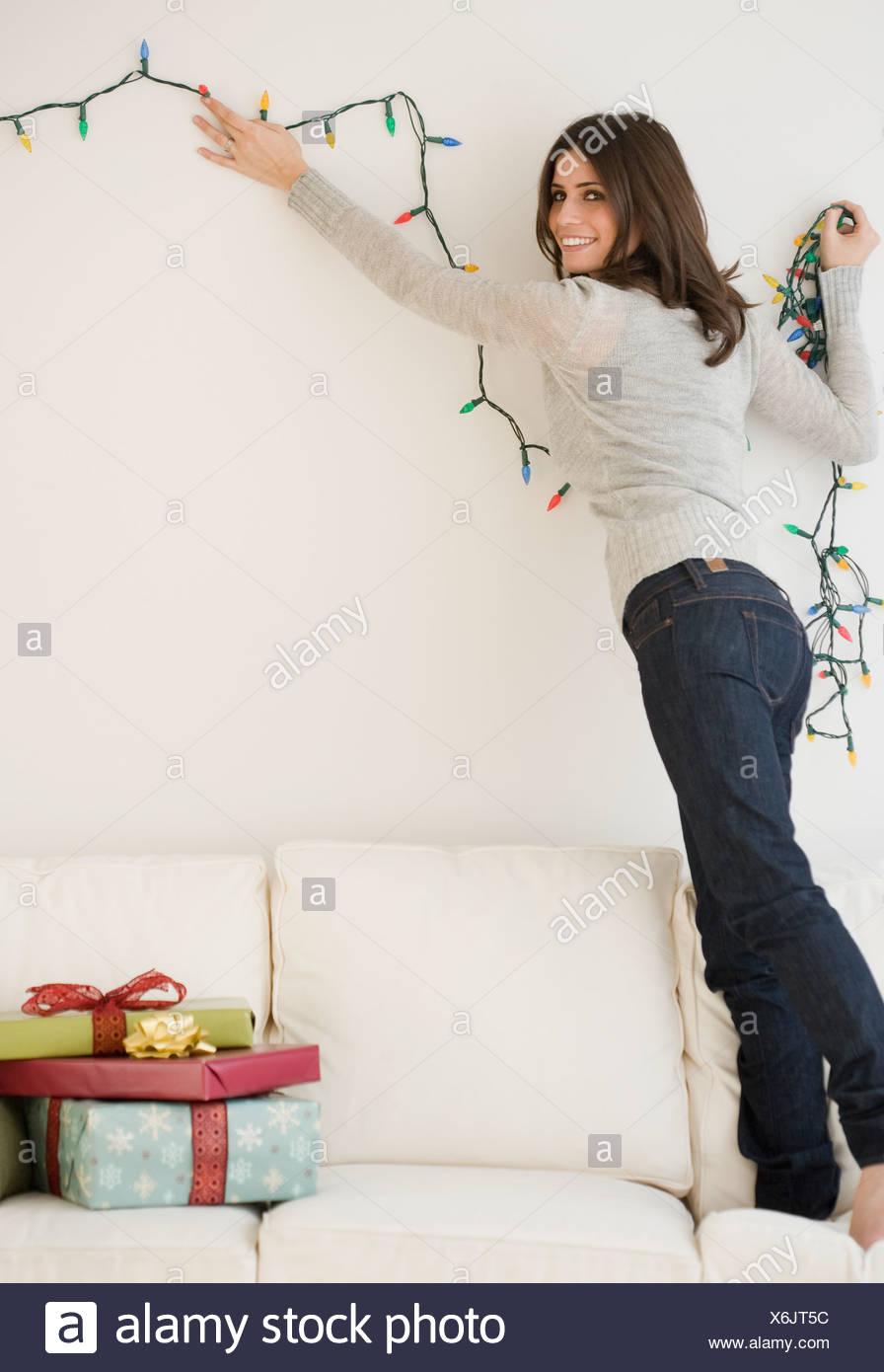 Woman hanging Christmas lights Stock Photo