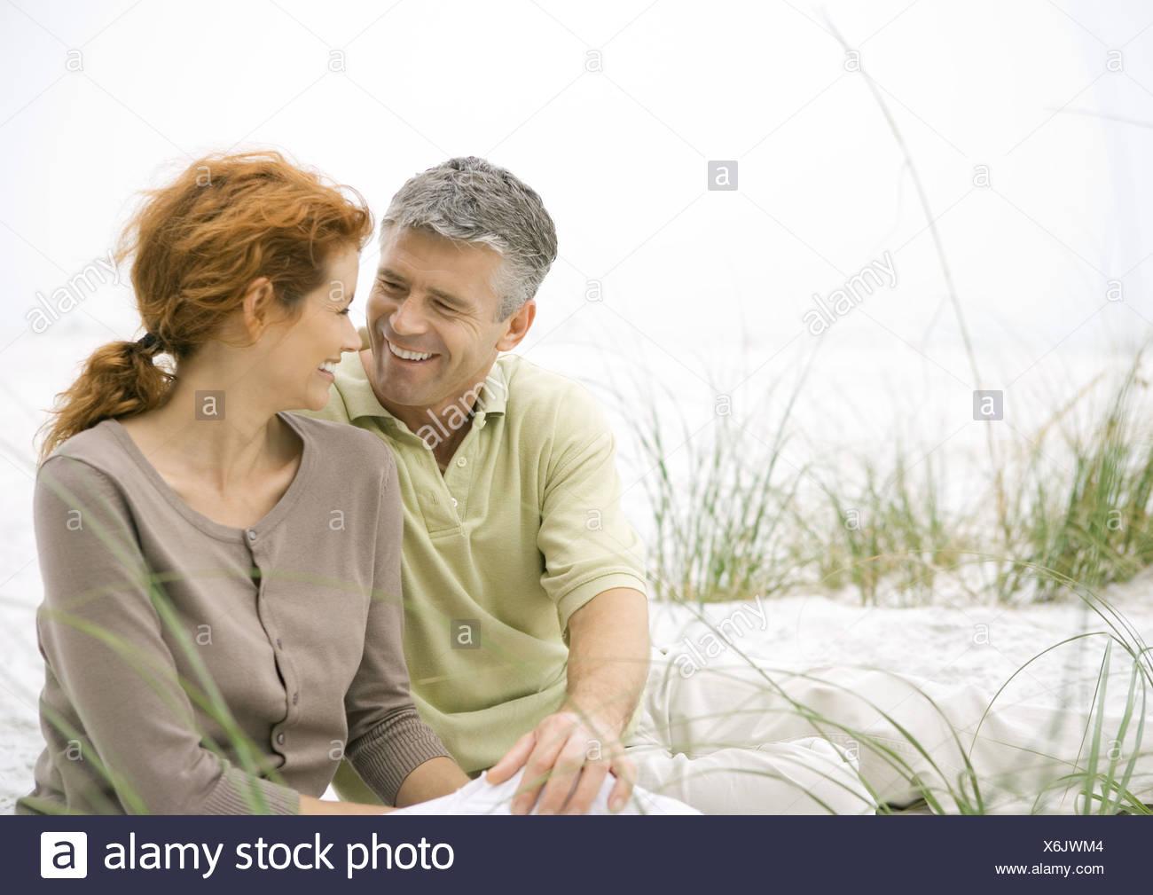 Mature couple sitting on beach Stock Photo