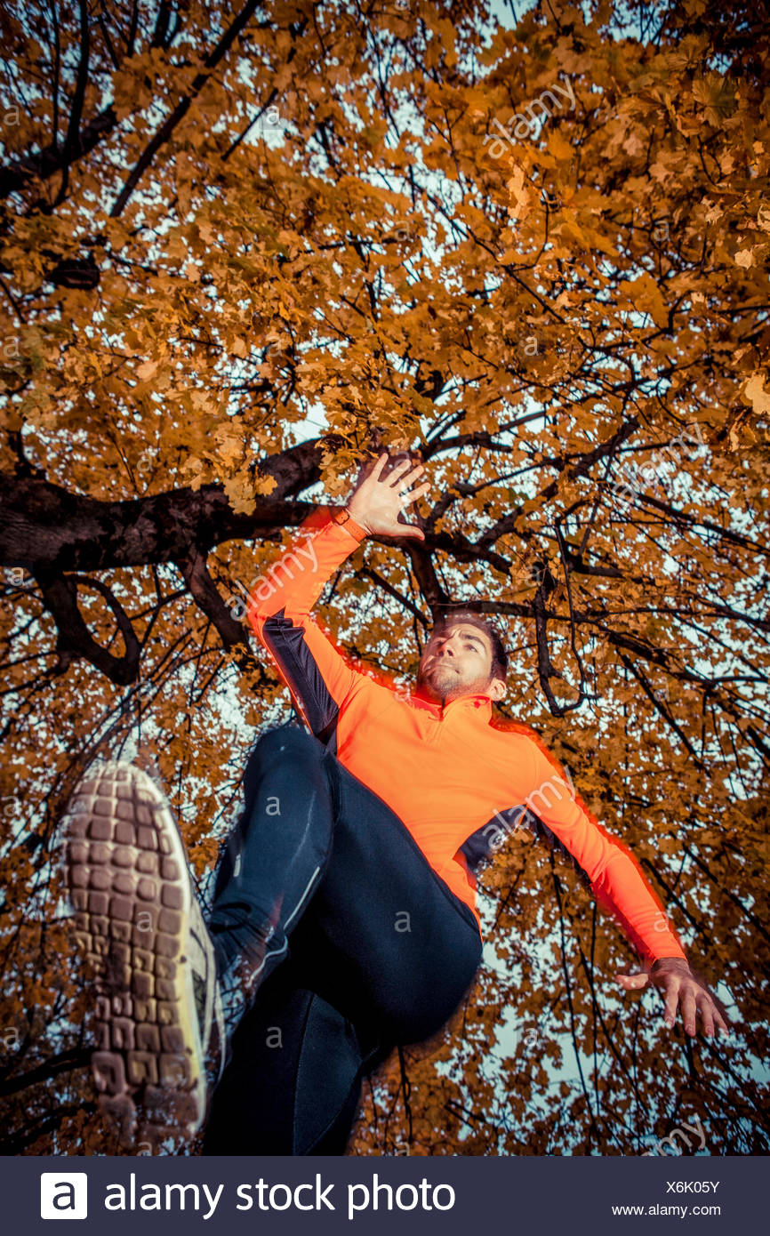 Male runner jumping and warming up in park - Stock Image