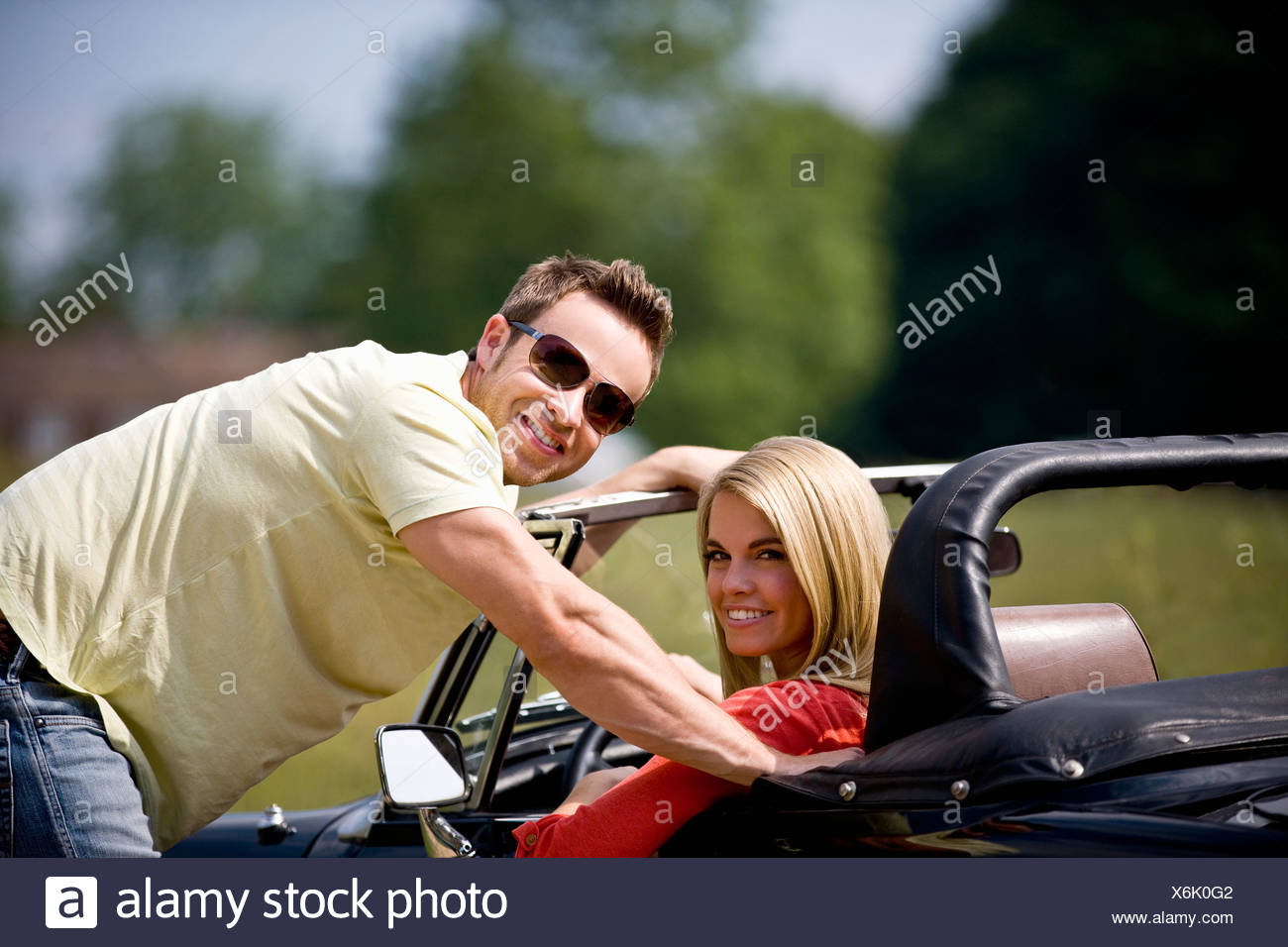 A young man standing next to a young woman in a black sports car Stock Photo