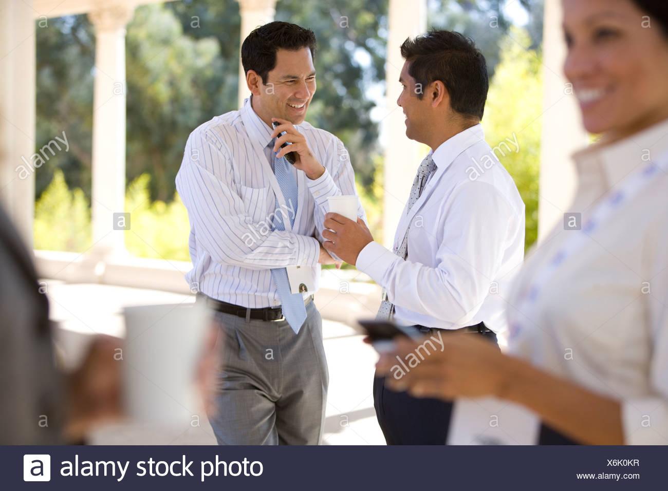 Businesspeople taking coffee break outdoors - Stock Image