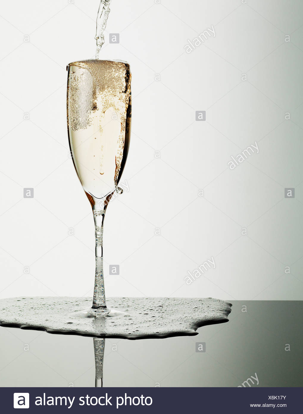 Champagne pouring into glass and overflowing Stock Photo
